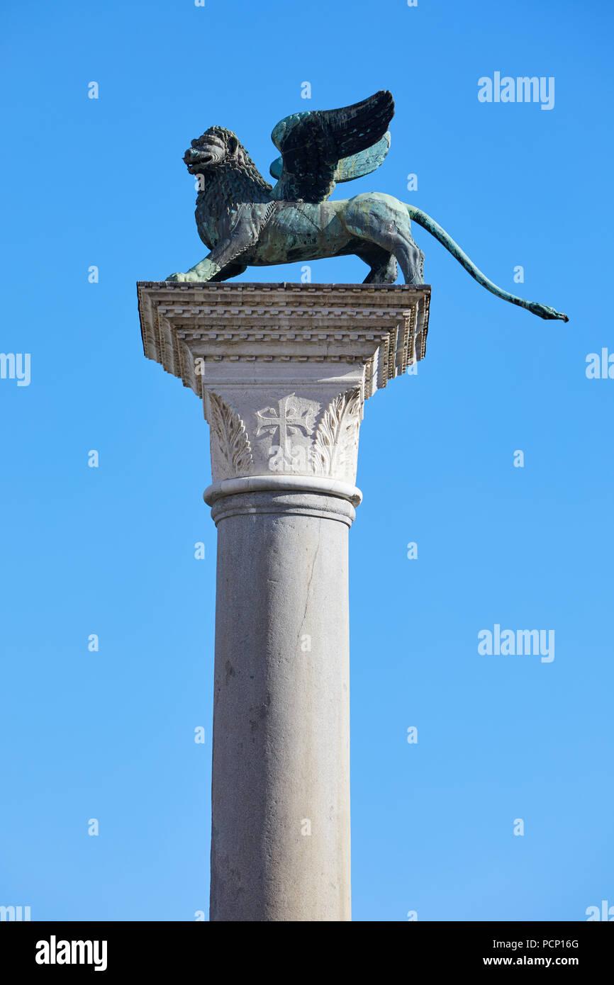Estatua del león alado, símbolo de Venecia en un día soleado, cielo azul en Italia Imagen De Stock