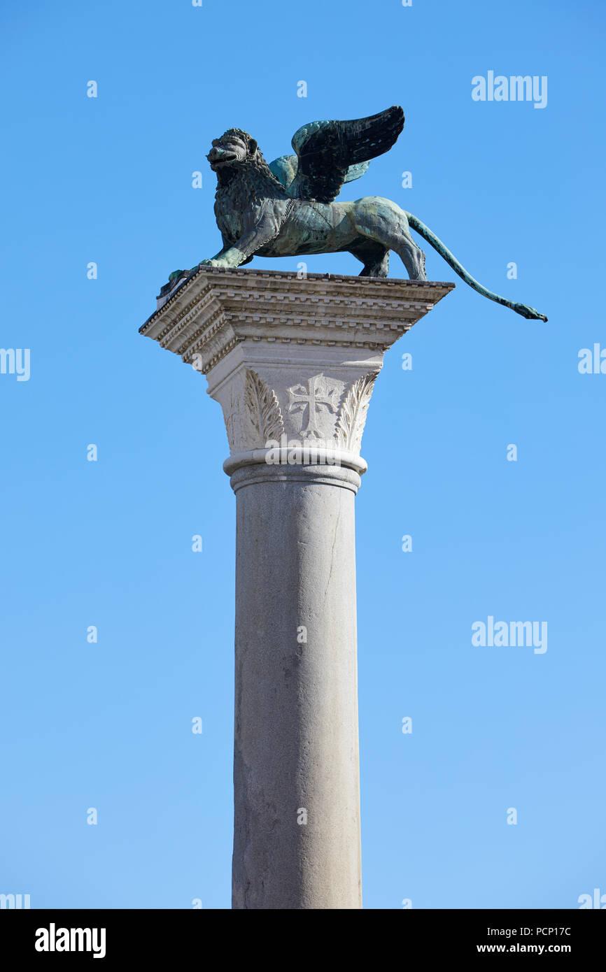 Estatua del león alado de San Marcos en la columna, símbolo de Venecia en un día soleado, cielo azul en Italia Imagen De Stock
