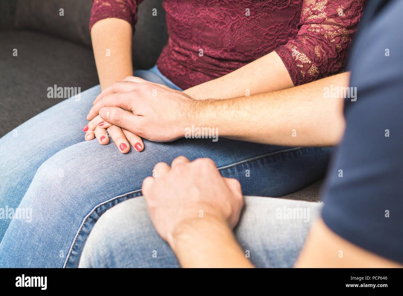 Novio disculpas a la novia. La pareja se apoyan mutuamente. Reconfortante o diciendo malas noticias. Joven Mujer sosteniendo la mano y reconfortante. Imagen De Stock