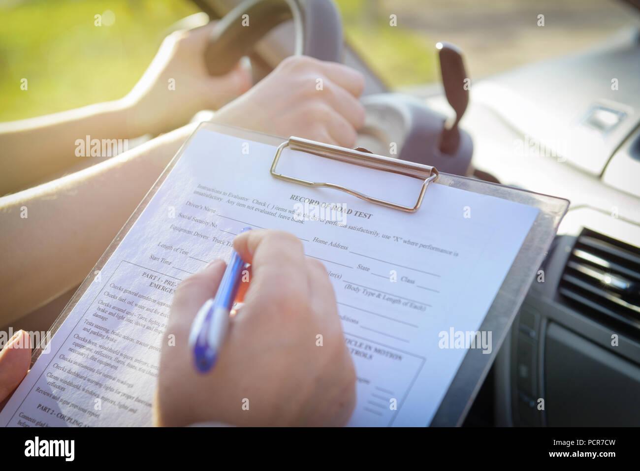 Examinador de llenado la licencia de conductor en forma de prueba en carretera sentado con su estudiante dentro de un coche Imagen De Stock