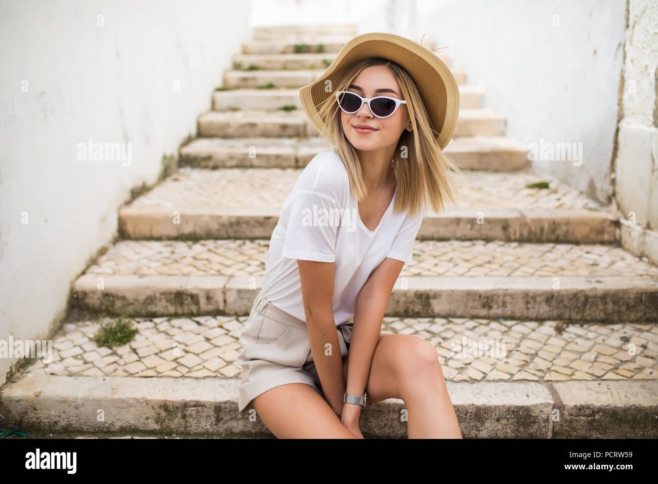 83a77fd55 Joven y bella mujer caucásica sonriendo en el contexto urbano. Chica rubia  vistiendo ropa casual