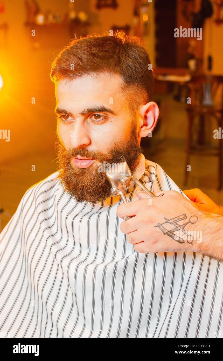 Barbero corta una barba de vintage de cortar el pelo a un joven guapo con barba y bigote. Hombre de peluquería. Imagen De Stock