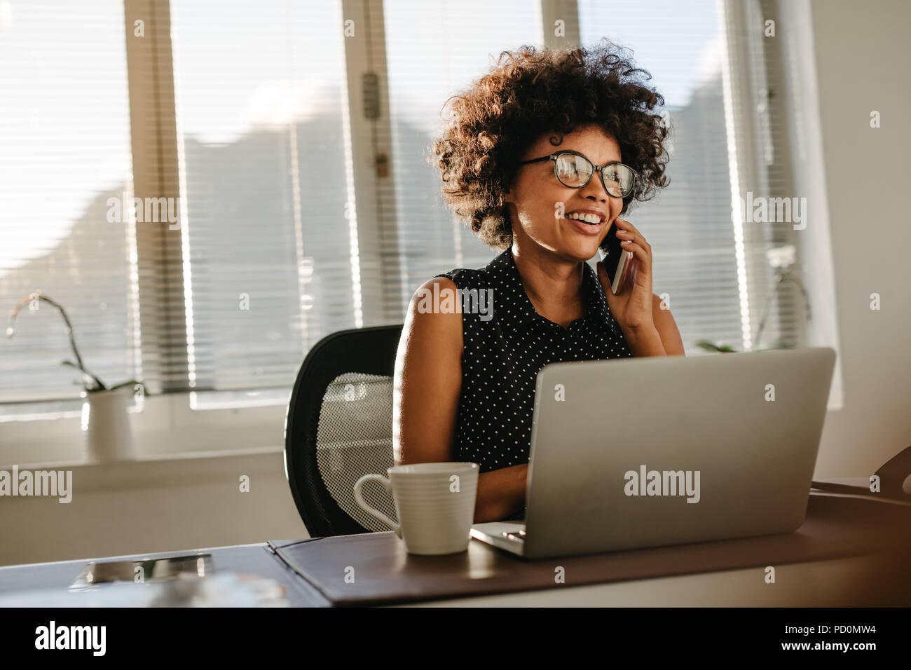 Joven africana trabajaba en su escritorio con ordenador portátil y hablando por teléfono. Mujeres vistiendo vestimenta casual inicio trabaja en una oficina. Imagen De Stock