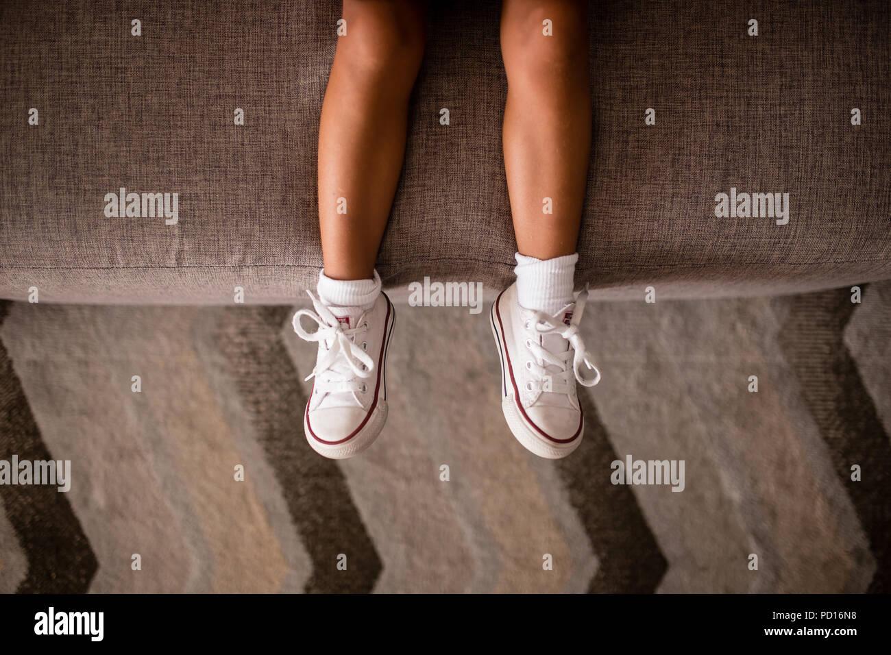 f1b63ec179 Las niñas las piernas en el sofá con zapatos blancos con detalles en rojo.  Patrón