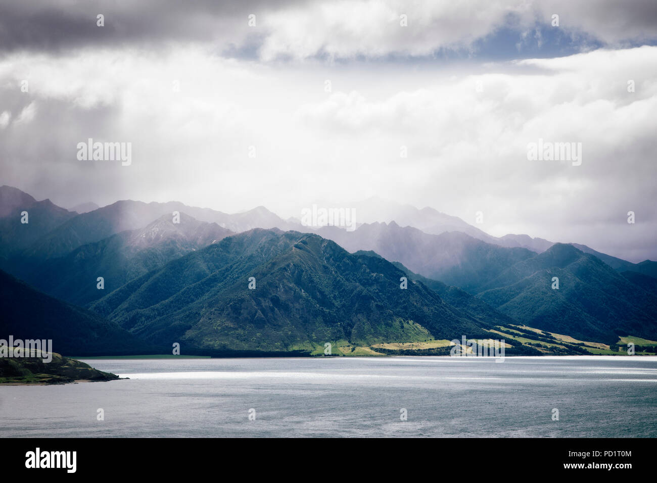 Las nubes y el sol atravesando el lago Hawea, Isla del Sur, Nueva Zelanda. Imagen De Stock