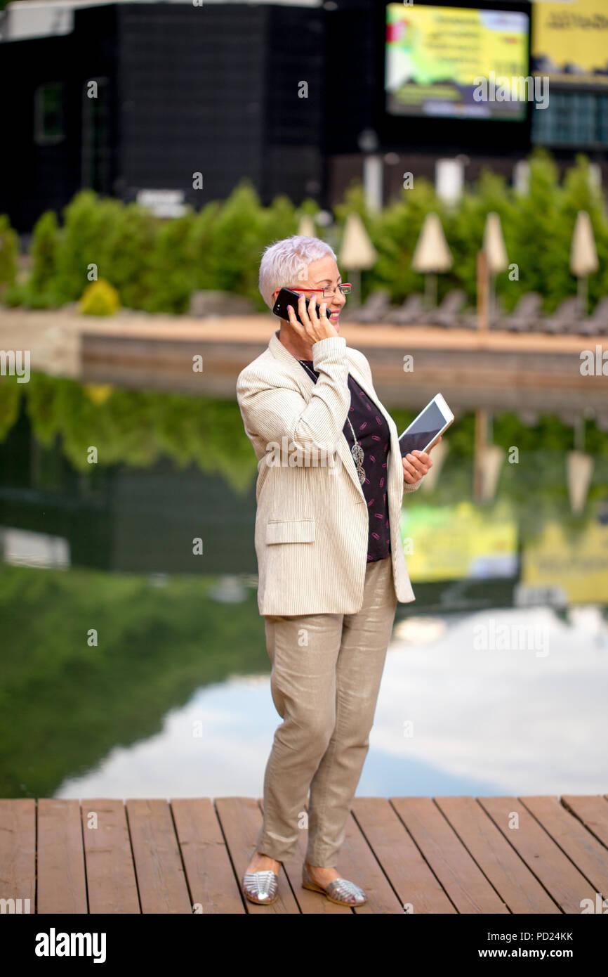 Longitud completa positivo retrato de mujer madura haciendo una llamada telefónica en el resort Imagen De Stock