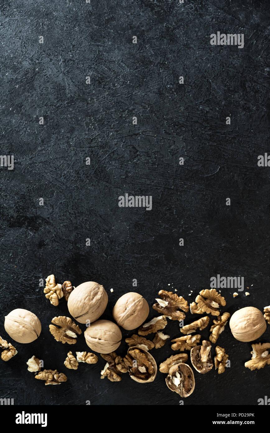 Nueces orgánicas. Las nueces en la frontera de piedra negra de fondo, vista superior, espacio de copia. Imagen De Stock