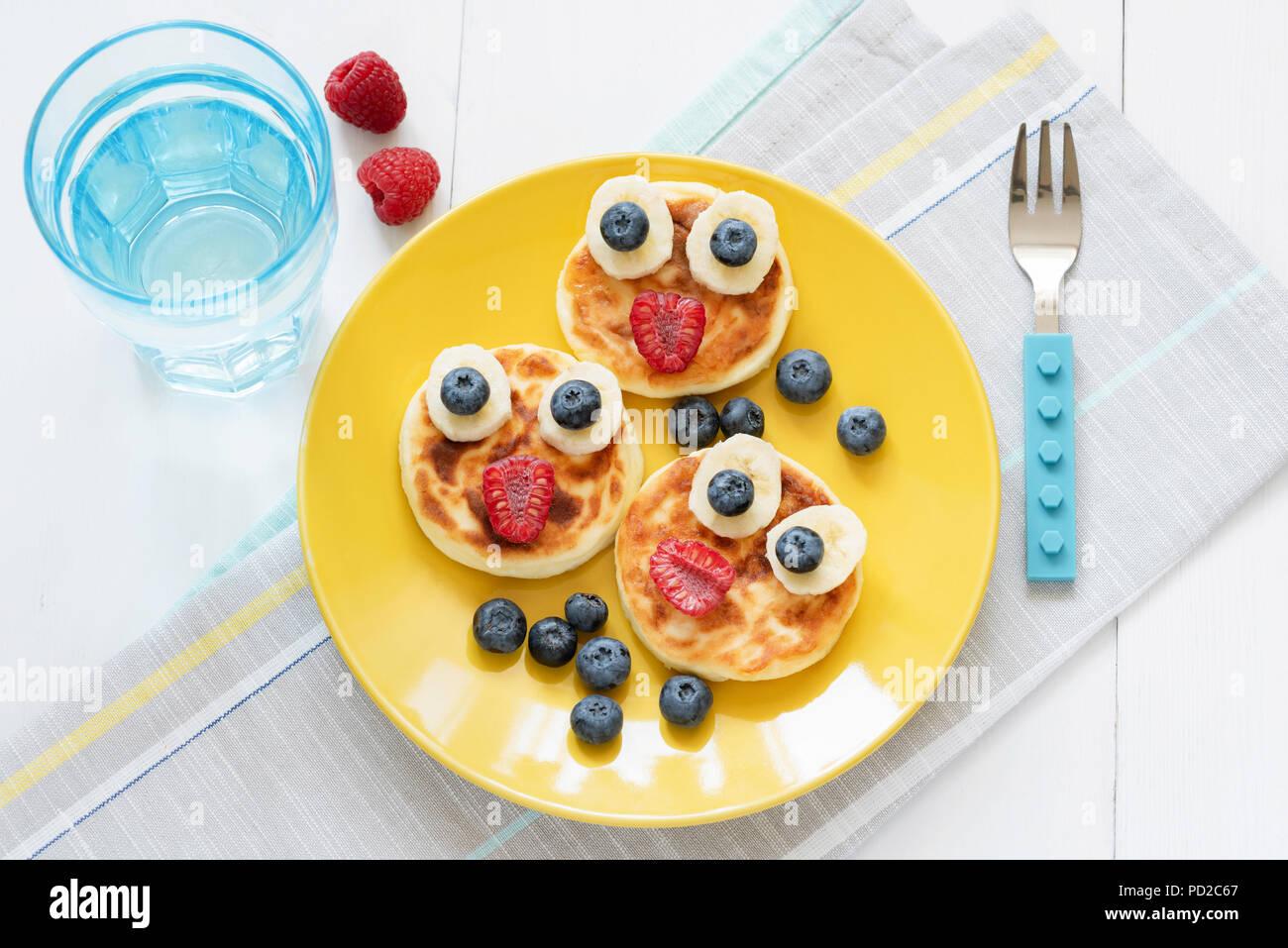 Desayuno para niños. Cara de animales divertidos panqueques con bayas frescas sobre placa amarilla y vaso de agua pura. Vista superior Imagen De Stock