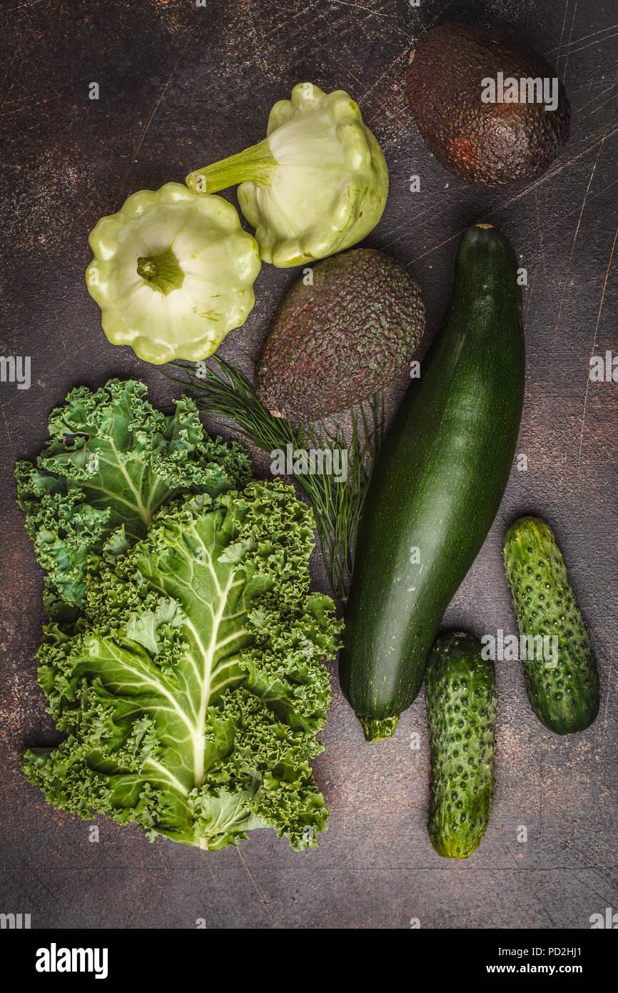 Surtido de verduras verdes sobre fondo oscuro, vista superior. Las frutas y verduras que contienen clorofila. Imagen De Stock