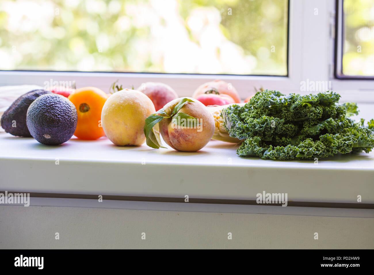 Frutas y verduras de temporada de verano en el alféizar de la ventana. Concepto de comer sanas y limpias. Imagen De Stock