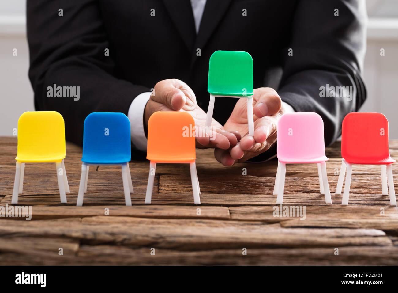 La mano del empresario recogiendo sillón verde entre otros en un mostrador de madera Imagen De Stock