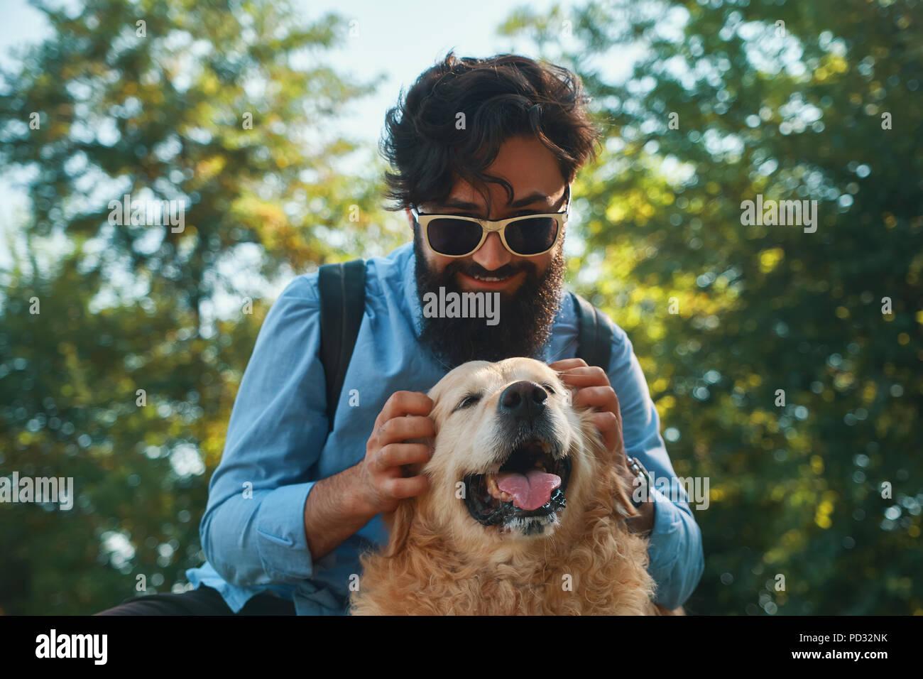 Hombre y el perro a divertirse, jugar, hacer muecas mientras restin Imagen De Stock