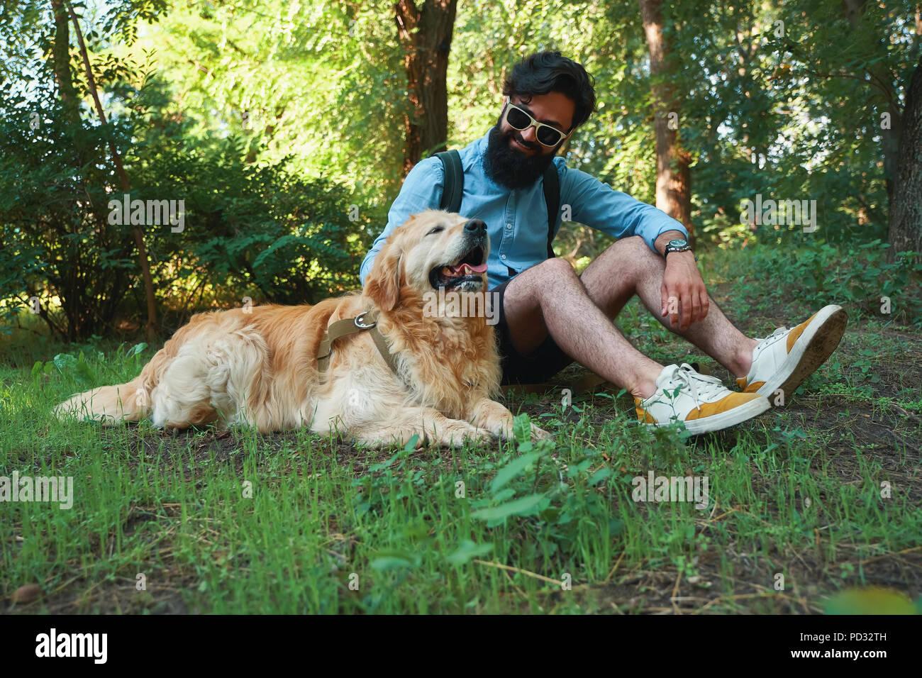 El hombre con la barba y su pequeño perro amarillo sol jugando y disfrutando Imagen De Stock