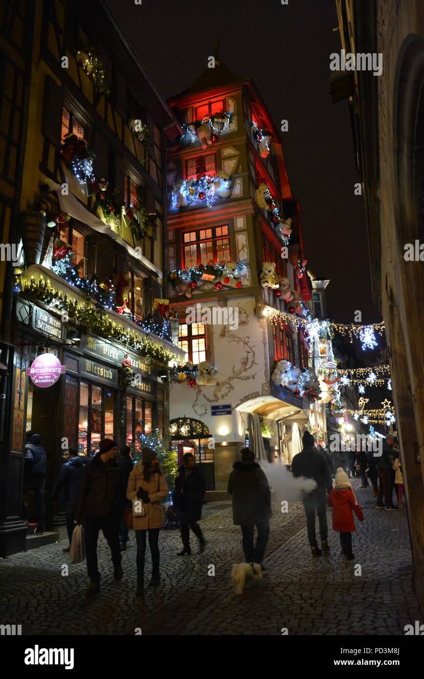 Una antigua y hermosa calle con las luces de Navidad y mucha gente caminando hacia arriba y hacia abajo. Numerosos pubs, restaurantes y tiendas. Imagen De Stock