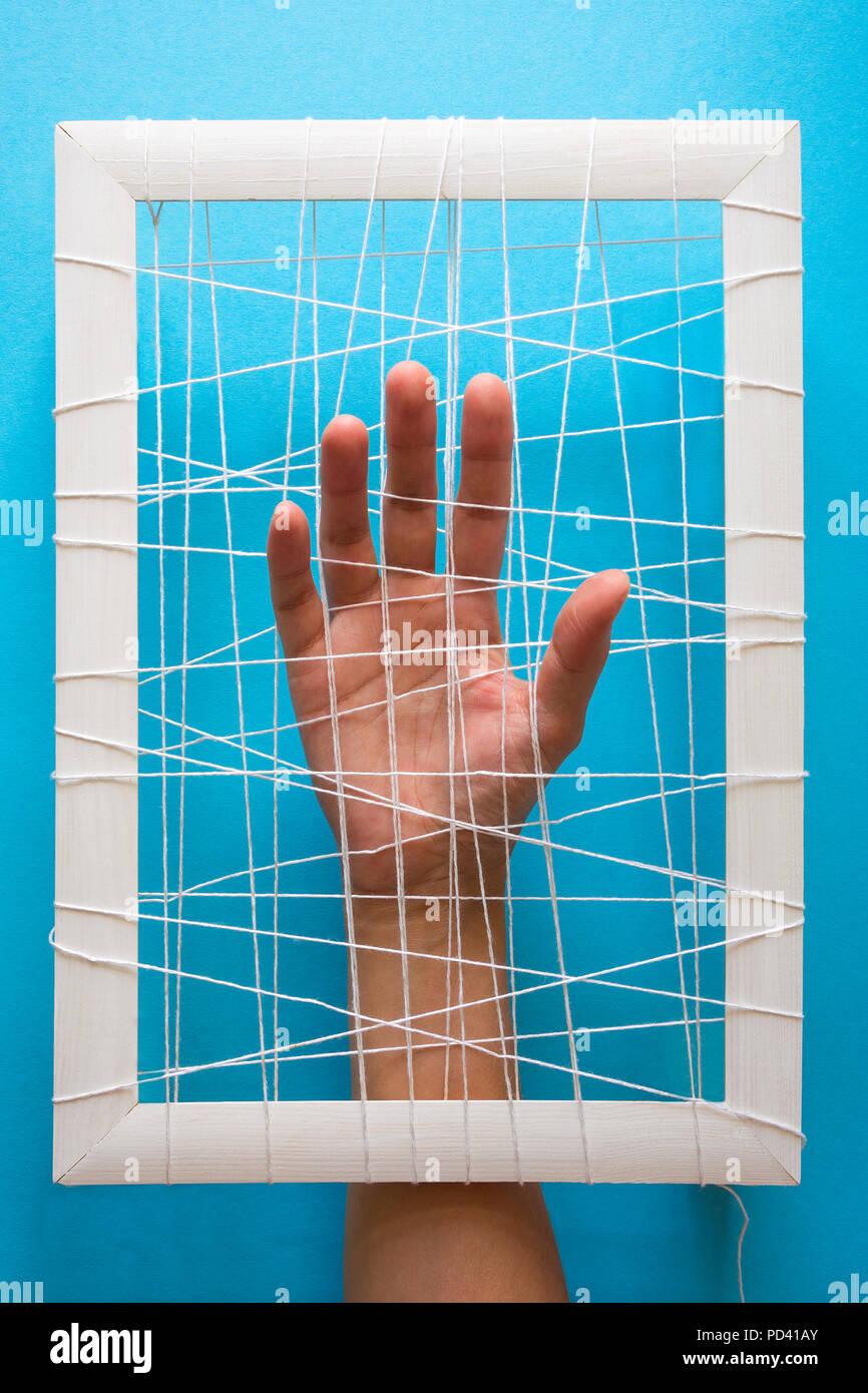 Concepto de salud mental. Manos de mujer intenta romper las cadenas sobre fondo azul. Imagen De Stock