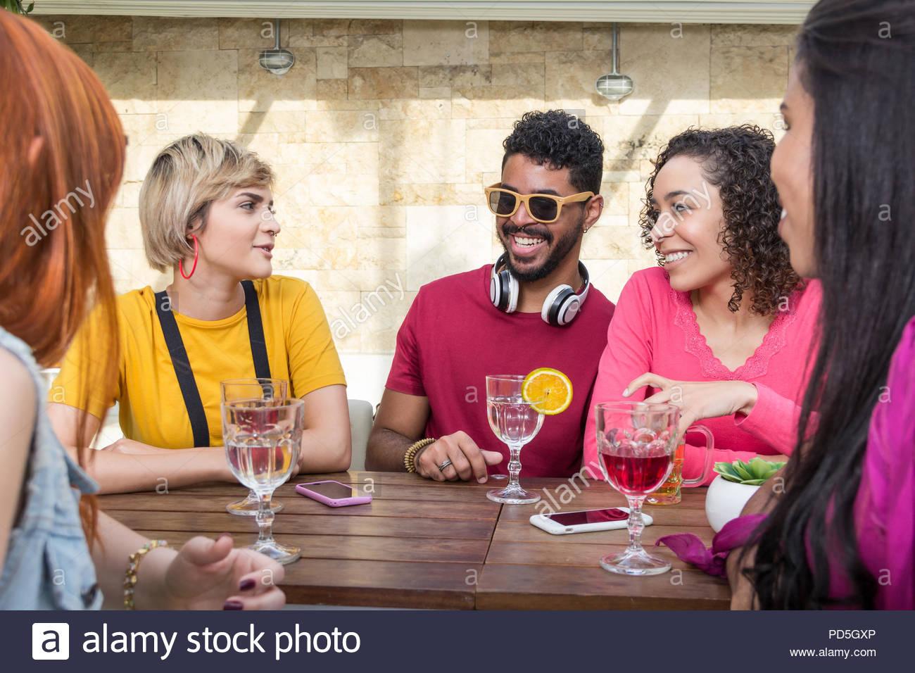 Grupo de jóvenes colgando fuera, divertirse en el restaurante exterior. Los estudiantes universitarios de fiesta juntos en la cafetería al aire libre. La primavera, cálido togethernes Imagen De Stock