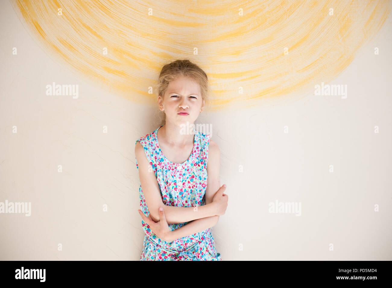 Muy molesto niña con mueca en su cara en vivo con la pared pintada de fondo de sun Imagen De Stock