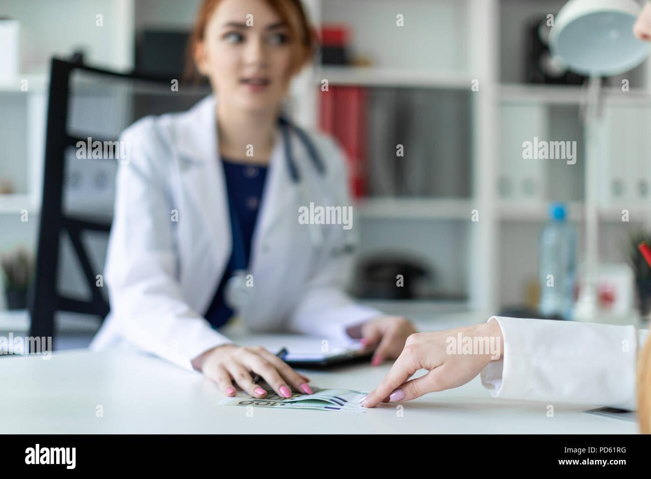 Una hermosa joven vestida con una túnica blanca está sentado en el escritorio de la oficina y la comunicación con el interlocutor. El interlocutor da la chica de dinero. Foto de stock