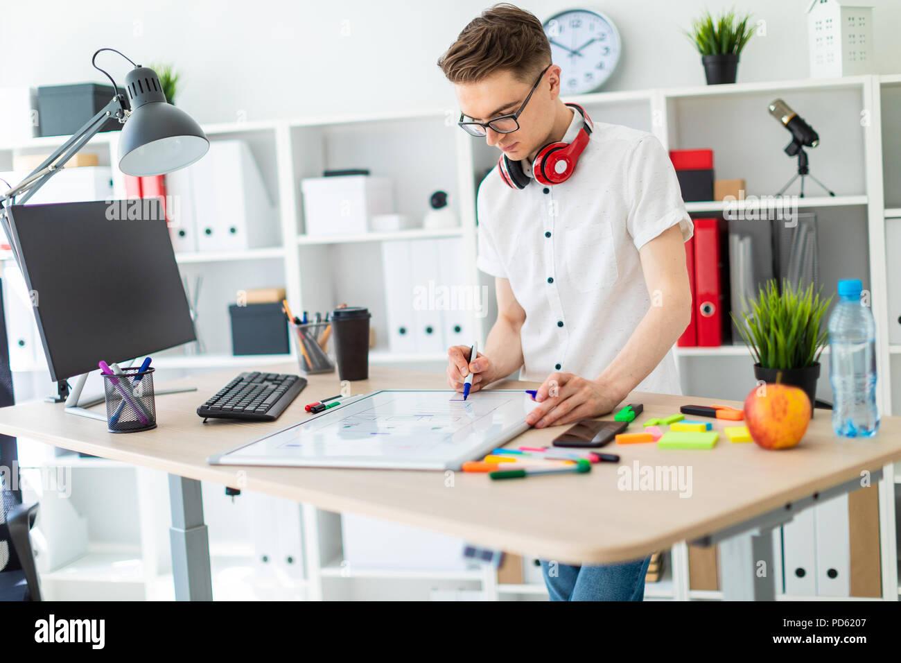 Un hombre joven en copas de pie cerca de una mesa de ordenador. Un hombre joven dibuja un marcador en un tablero magnético. En el cuello, el tío es colgar los auriculares. Foto de stock