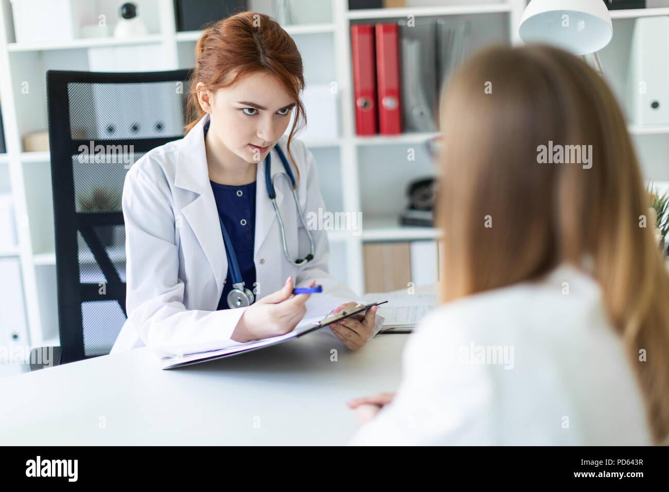 Una hermosa joven vestida con una túnica blanca está sentado en el escritorio de la oficina y la comunicación con el interlocutor. La niña toma notas en la hoja. Foto de stock