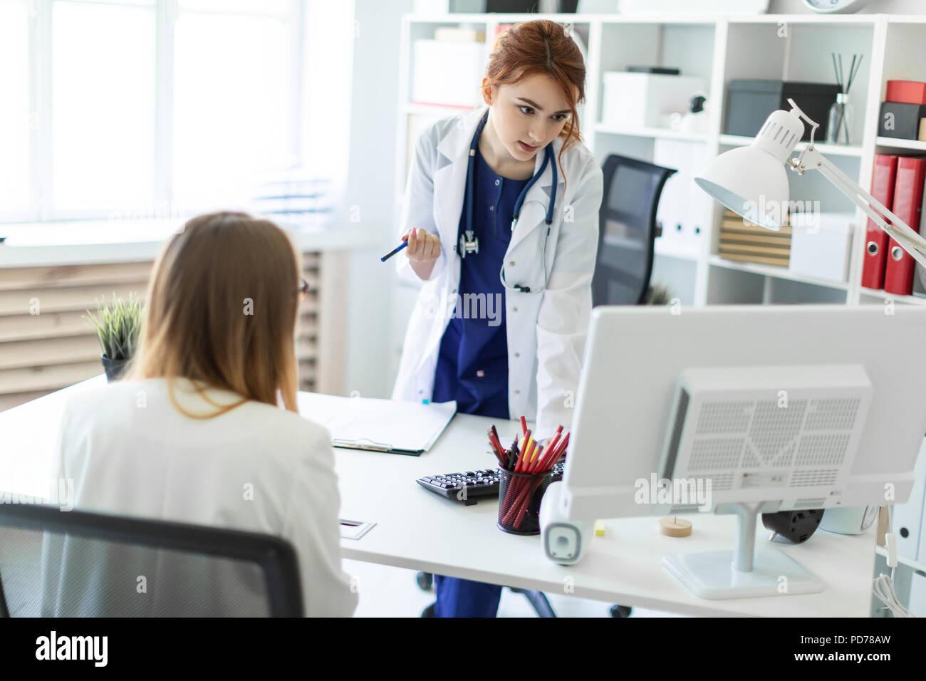 Una hermosa joven vestida con una túnica blanca está de pie cerca de una mesa de ordenador en la oficina y en la comunicación con el interlocutor. La chica hace notas en el documento. Foto de stock