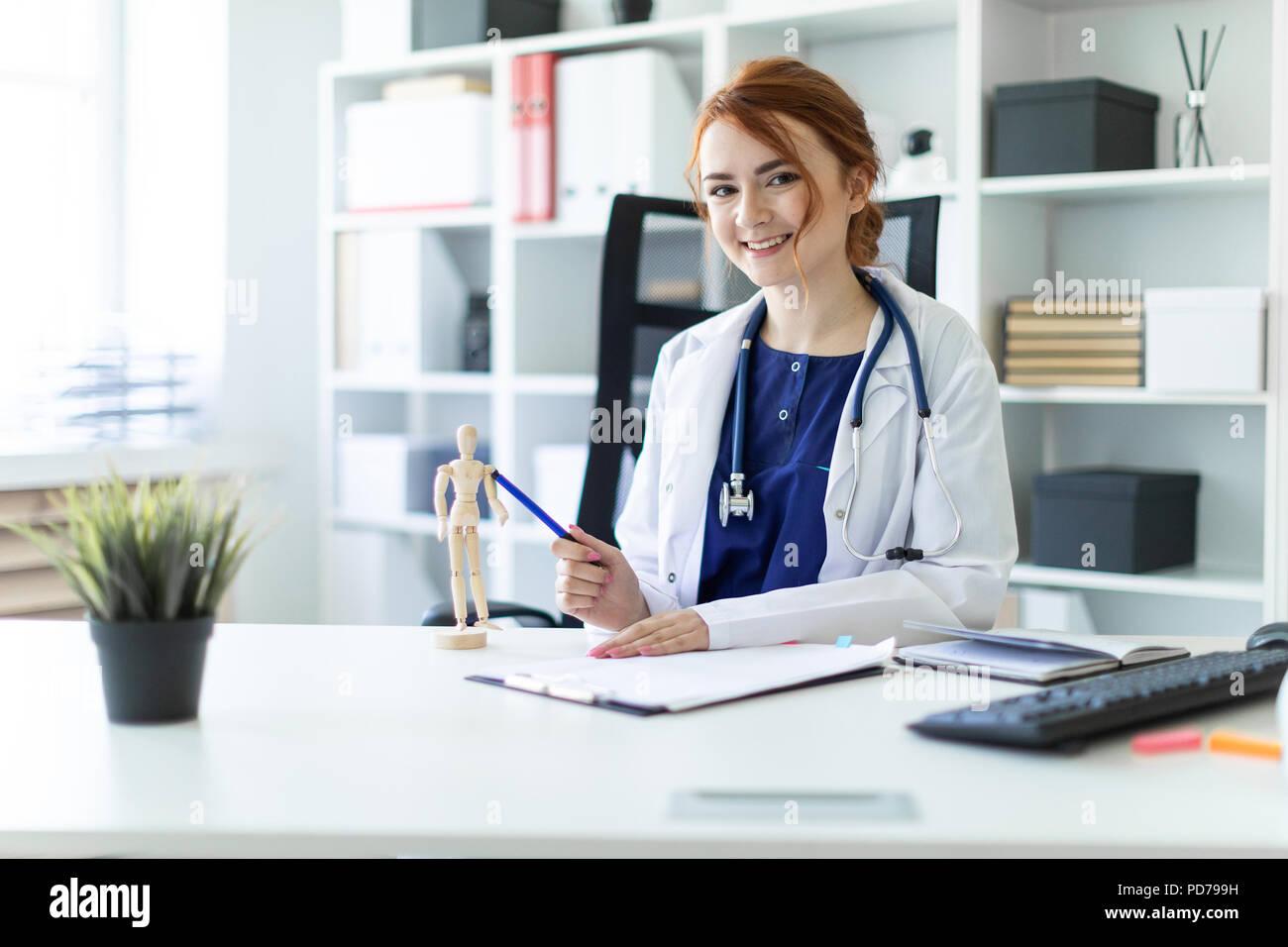 Una hermosa joven vestida con una túnica blanca está sentado en una mesa en la oficina. Foto de stock