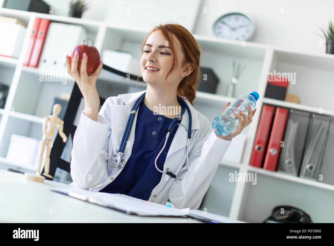 Una hermosa joven vestida con una túnica blanca se sienta en una mesa en la oficina y tiene una manzana y una botella de agua en su mano. Foto de stock