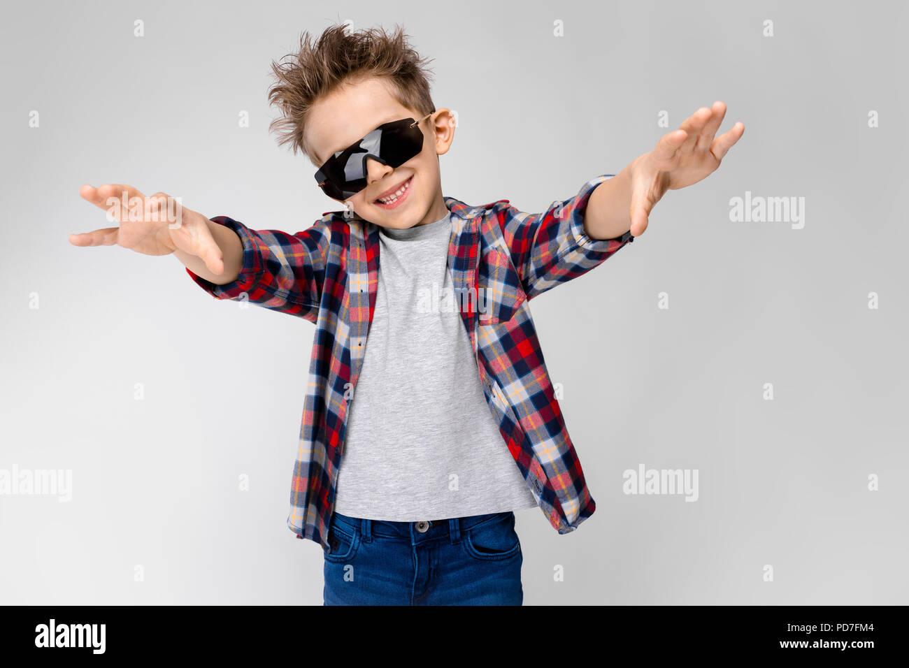fb0bc5c1a6 Un guapo muchacho en una camisa de cuadros escoceses, camiseta gris y jeans  destaca sobre