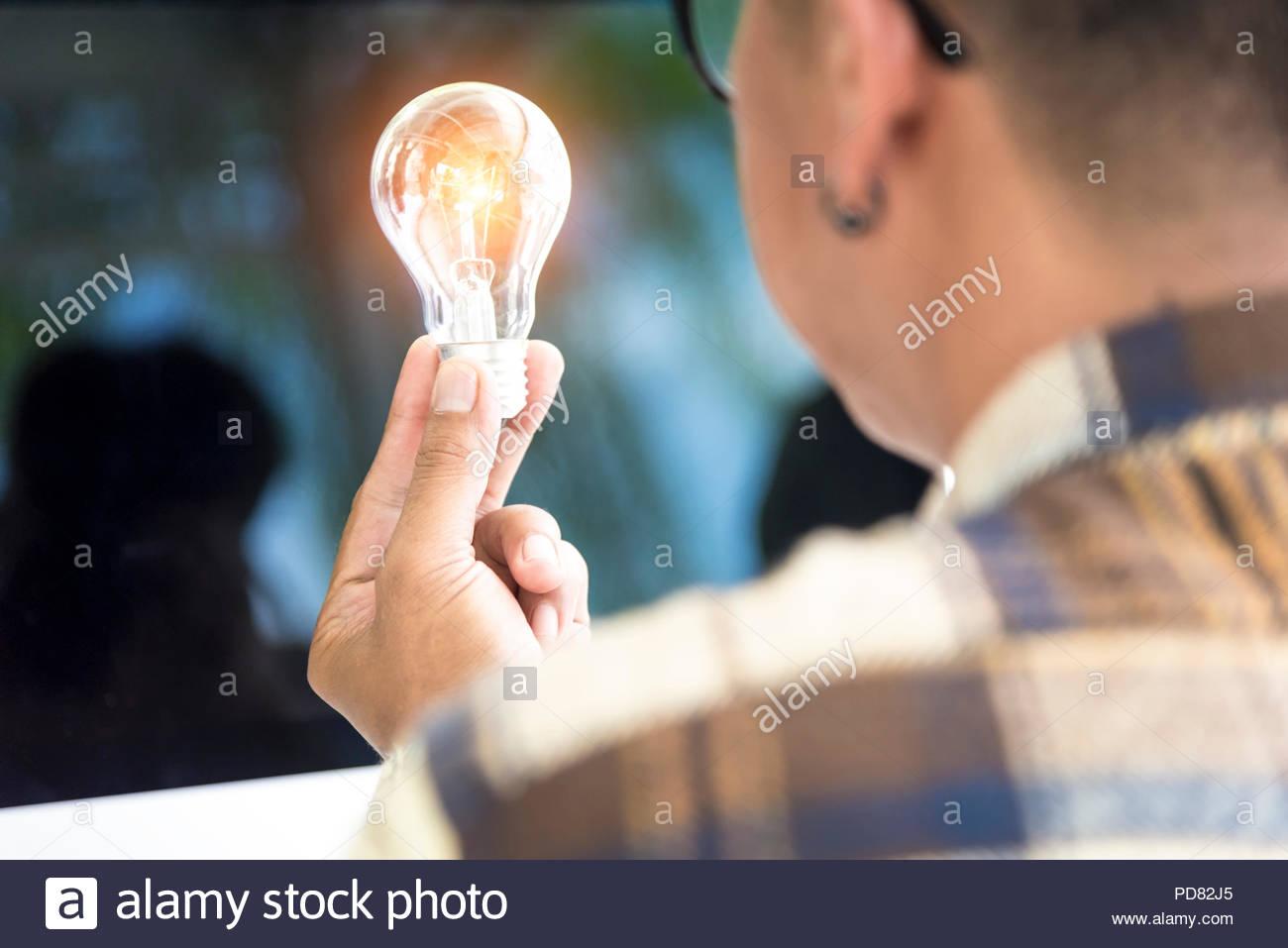 Diseñador creativo mirando la bombilla para pensar la nueva innovación idea Imagen De Stock