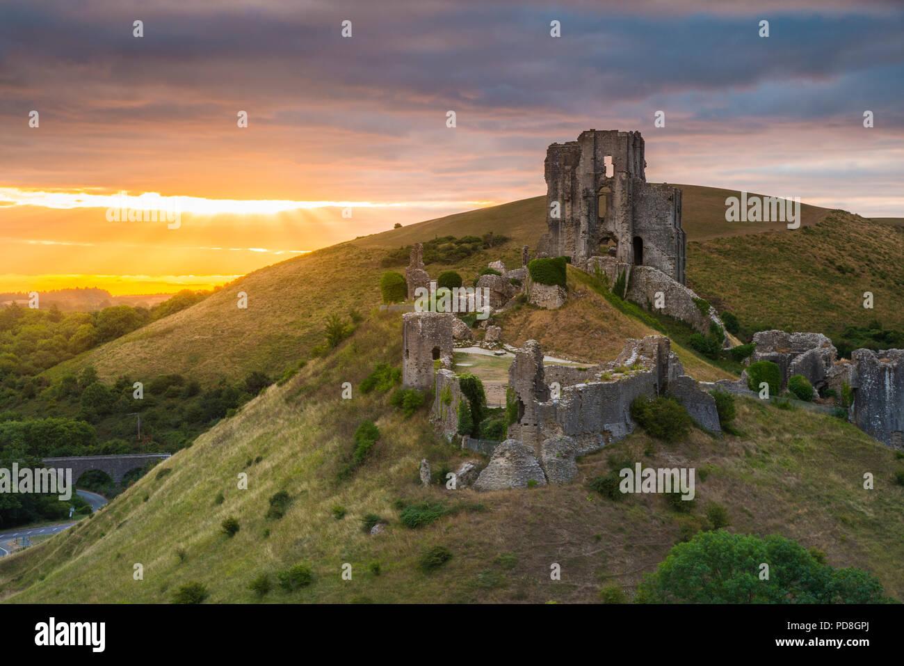 El castillo Corfe, en Dorset, Reino Unido. El 8 de agosto de 2018. El clima del Reino Unido. Un dramático amanecer en las ruinas de castillo Corfe, en Dorset. El amanecer fue pronto oscurecida por una banda de espesamiento de la nube que produjo ligeras lluvias poco después. Crédito de la imagen: Graham Hunt/Alamy Live News Imagen De Stock