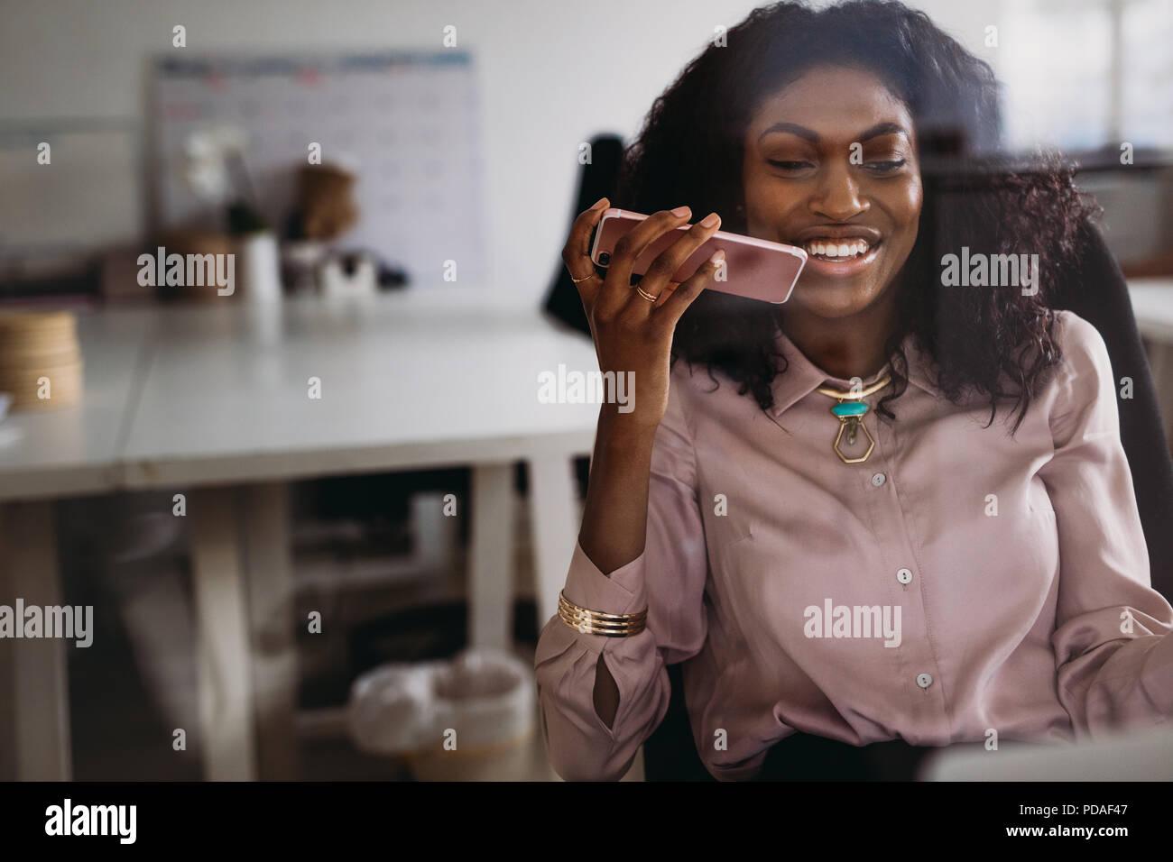 Empresaria en atuendo formal hablando a través del altavoz del teléfono móvil sentada en su casa. Empresaria administrar el negocio desde su casa discutiendo wor Imagen De Stock
