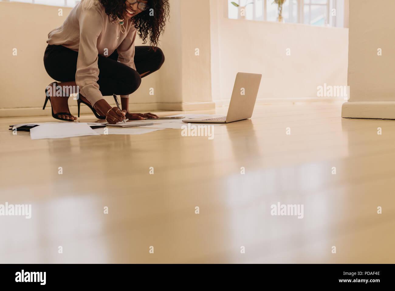 Mujer emprendedora en atuendo formal haciendo notas mientras trabaja en equipo portátil en casa. La empresaria sentado en suelo usar sandalias en casa maki Imagen De Stock