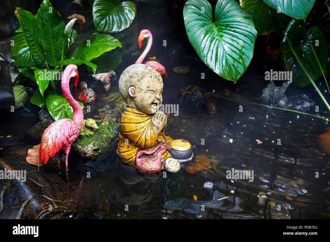 Estatua de poco monje budista en el jardín tropical con Pink Flamingo en Wat Saket Golden Mountain templo en Bangkok Foto de stock
