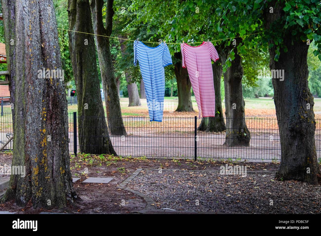 Trajes de baño anticuado stripey colgando de una línea entre los árboles a Badehaus-Garten,Tollensee,Neubrandeburg,Mecklenburg Lake District Imagen De Stock