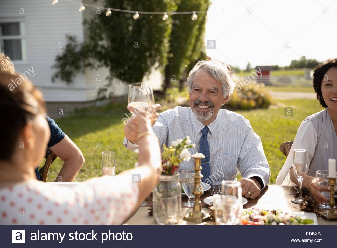 Hombre y mujer celebrando, copas de vino tostado en el Sunny garden party almuerzo Imagen De Stock