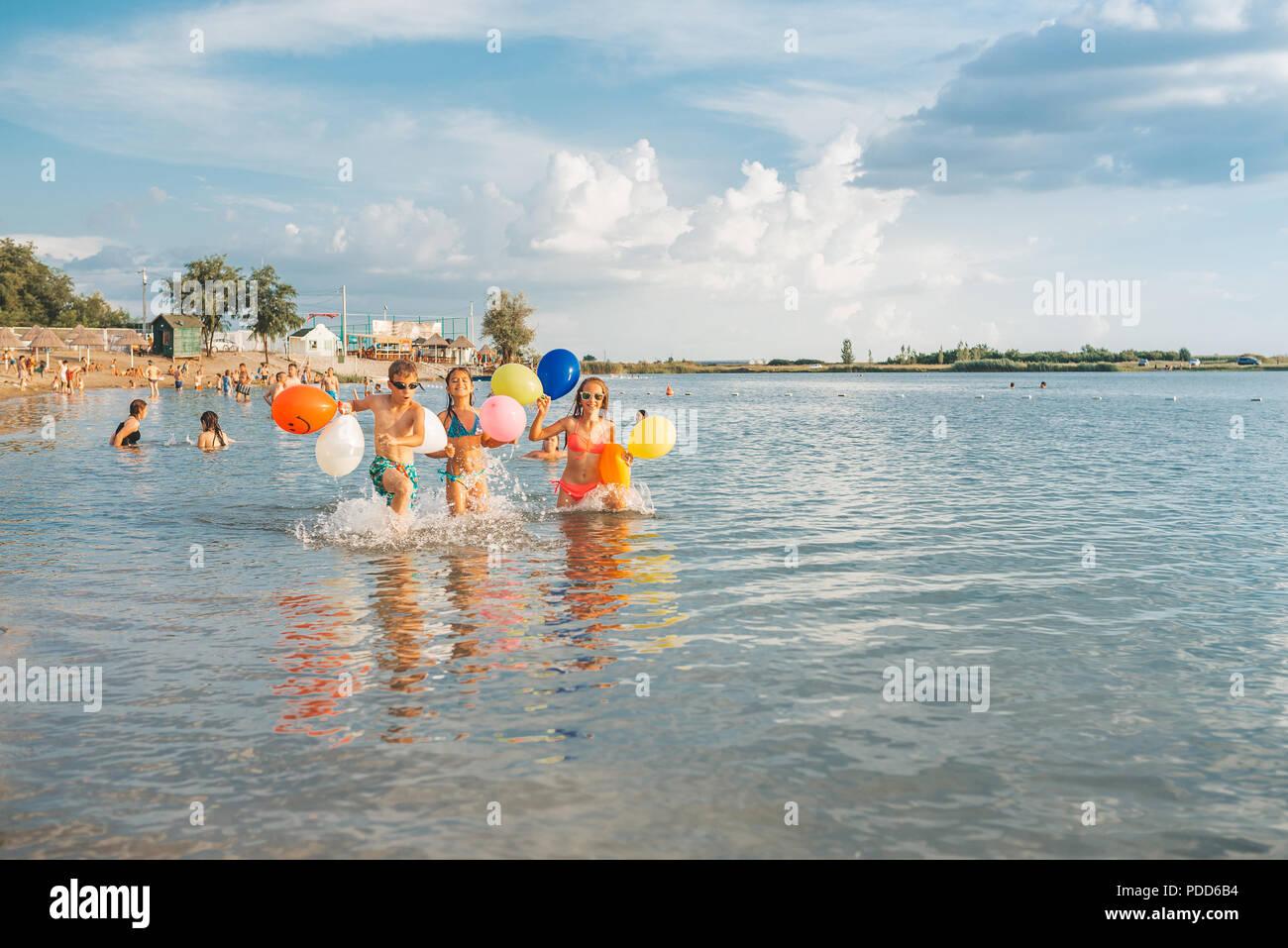 Niños felices jugando en el mar. Los niños divertirse al aire libre. Vacaciones de verano y el concepto de estilo de vida saludable Imagen De Stock