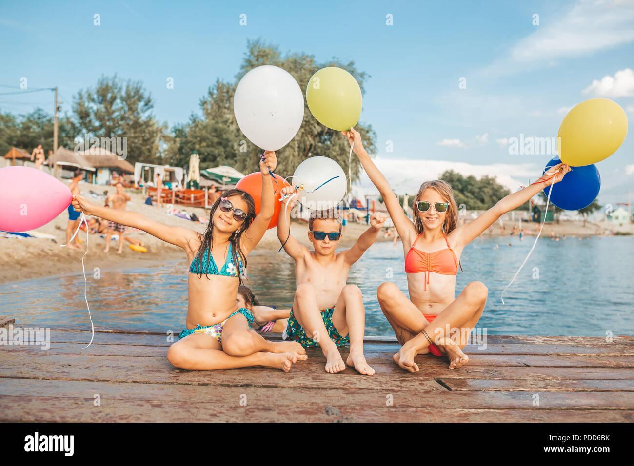 Niños felices jugando con los globos en el mar. Los niños divertirse al aire libre. Vacaciones de verano y el concepto de estilo de vida saludable Imagen De Stock