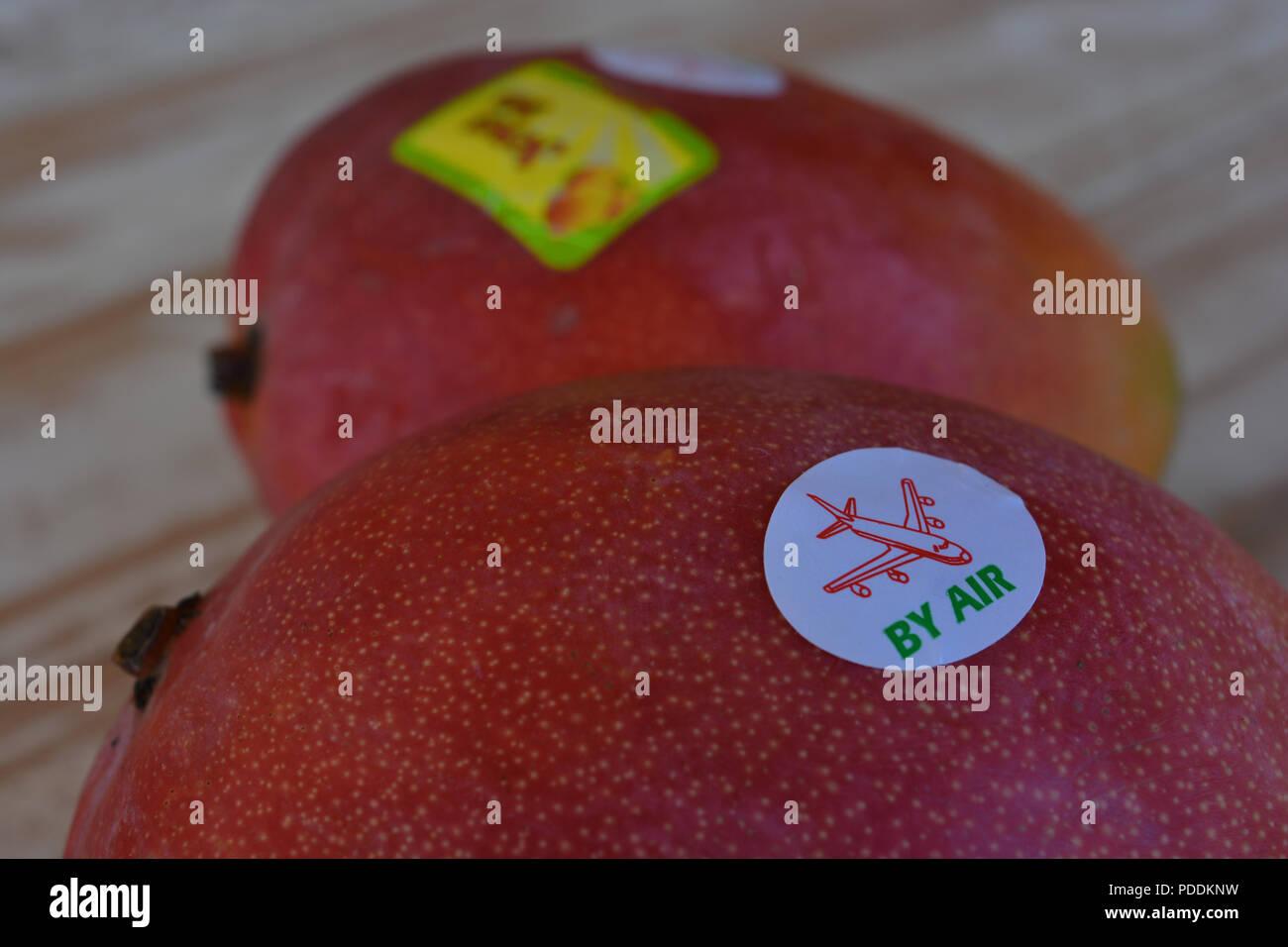 Por aire pegatina de mango fresco de frutas en un supermercado de Gran Bretaña. Imagen conceptual, la huella de carbono. Imagen De Stock