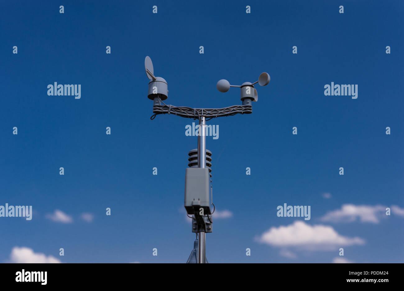 Estación meteorológica casera sobre un fondo de cielo azul con el sol detrás de las nubes. Medición de la temperatura, la humedad y la dirección del viento Foto de stock