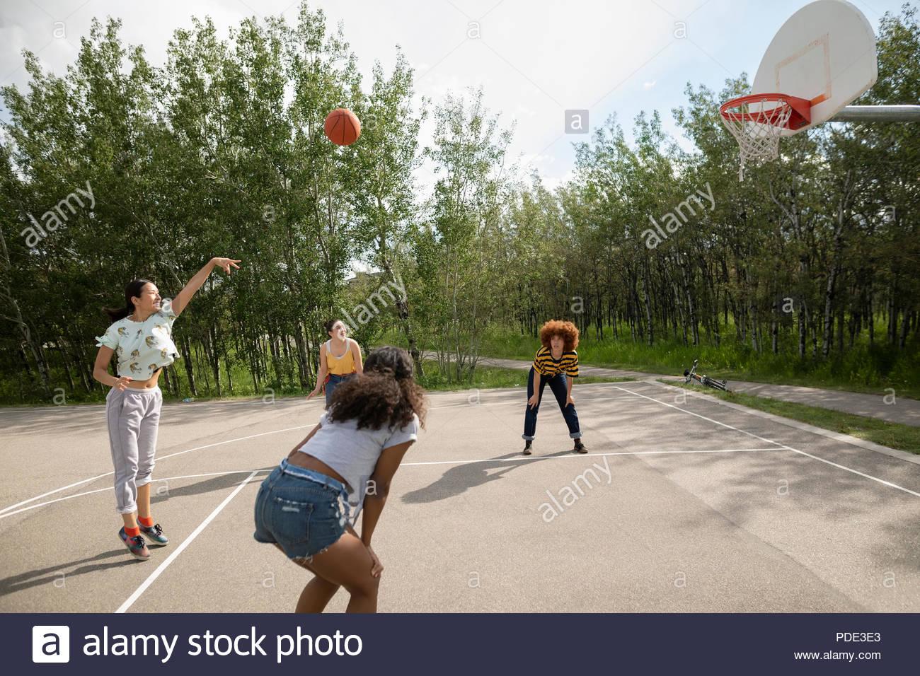 Adolescente amigos jugando baloncesto en la cancha de basketball del Parque Imagen De Stock