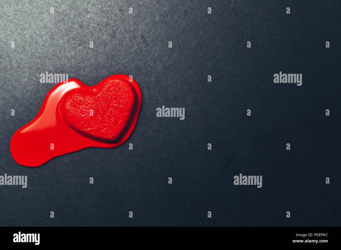 Helados con forma de corazón rojo fusión oscura o negra sobre un papel con textura de fondo. Concepto de verano, amor y corazón romper Imagen De Stock