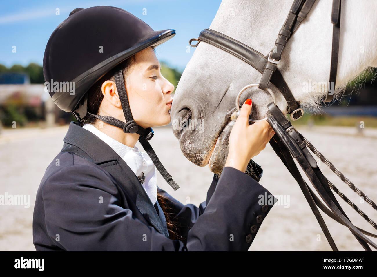Amazona amorosa con rojo nail art besando a su caballo blanco Imagen De Stock