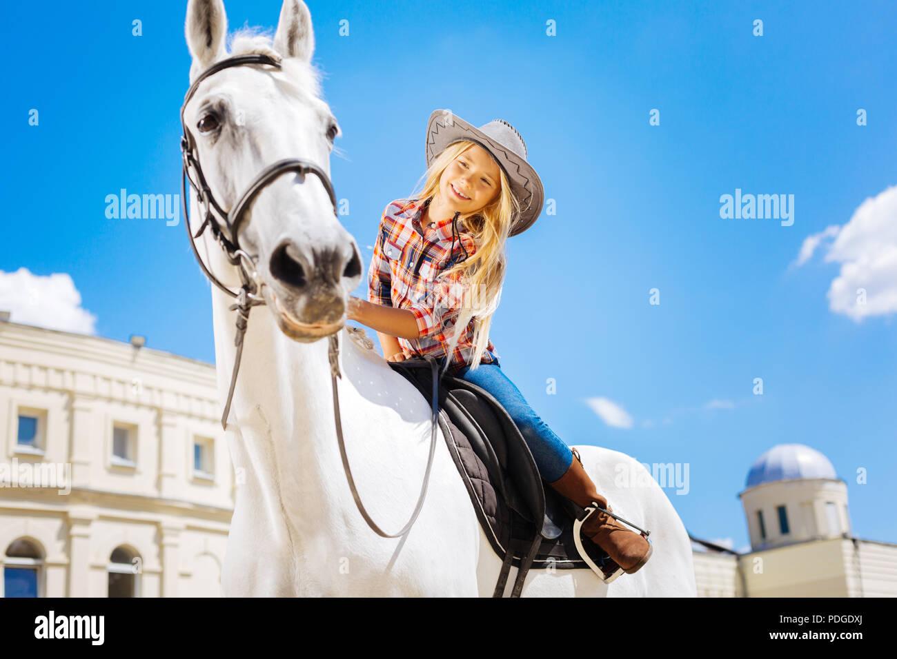 Transmisión de colegiala tocando su blanco caballo de carreras Imagen De Stock