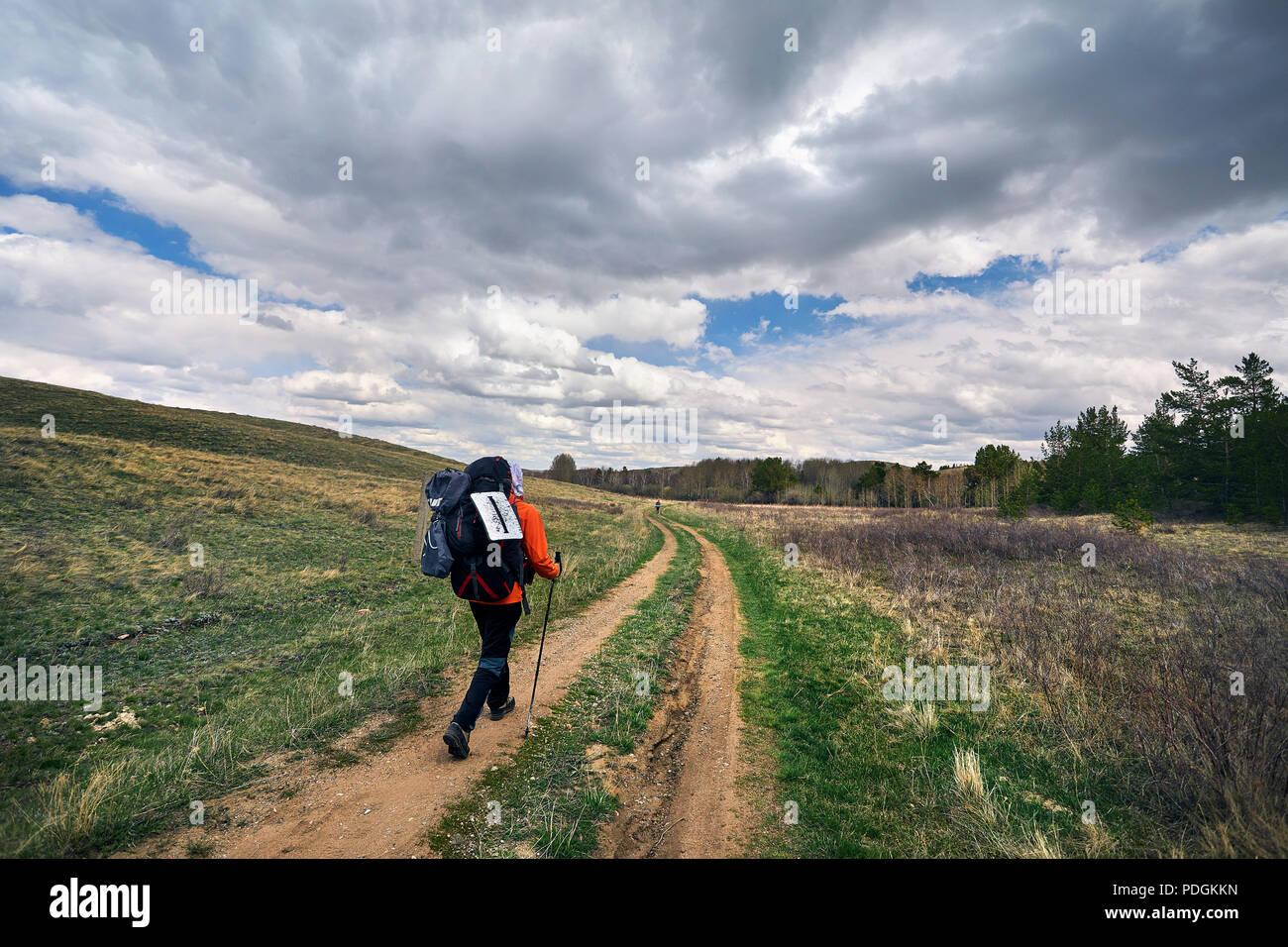 Excursionista con big mochila caminando por la carretera cerca del bosque contra el cielo nublado en Karkaraly national park en el centro de Kazajstán Foto de stock