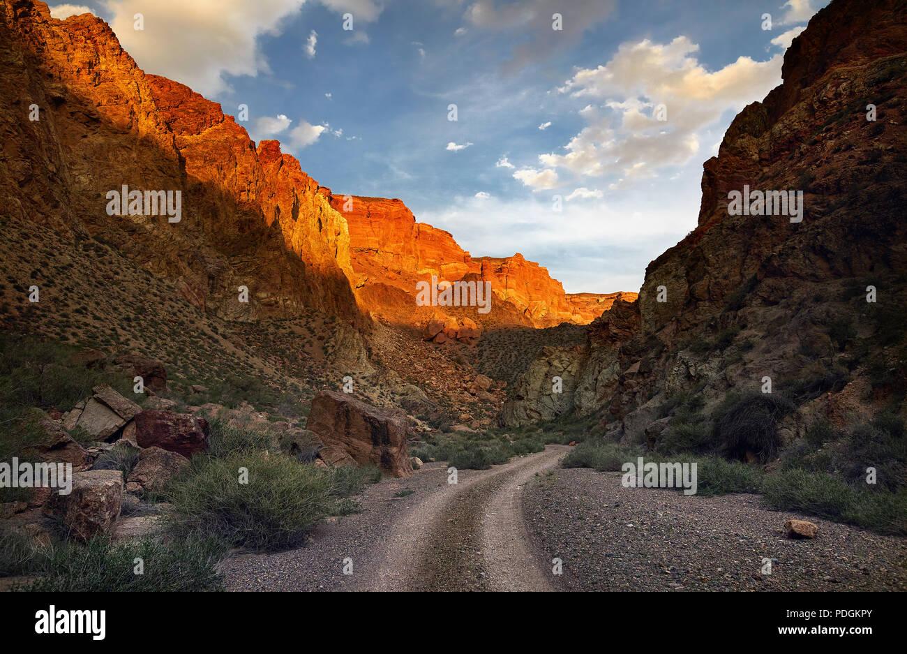 Rocas de color naranja y carretera a Cañón Charyn al atardecer en Kazakhsthan Foto de stock