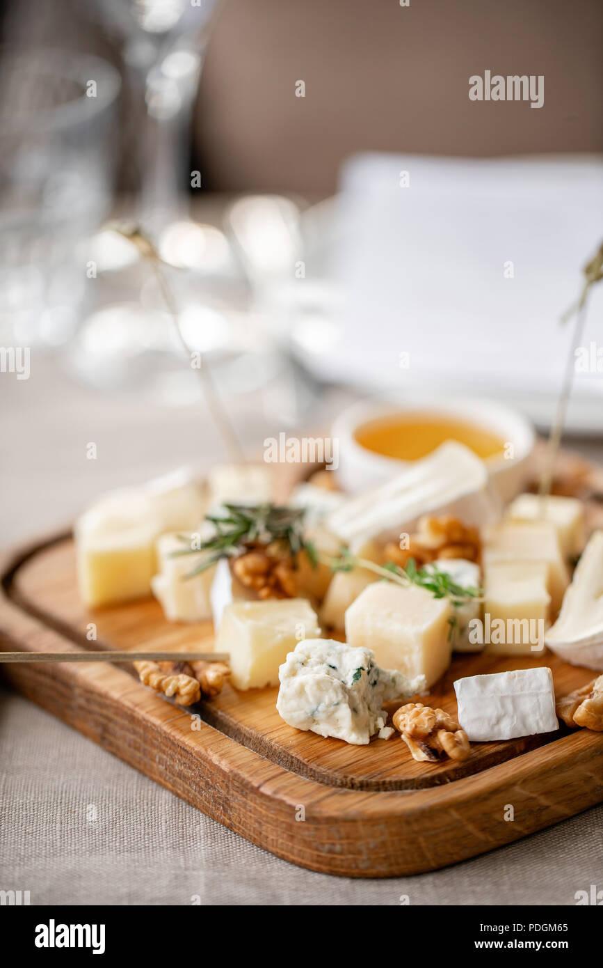 Plato de queso. Una deliciosa mezcla de queso con nueces, miel sobre la mesa de madera. Plato de degustación en una placa de madera. Alimentos para el vino. Foto de stock