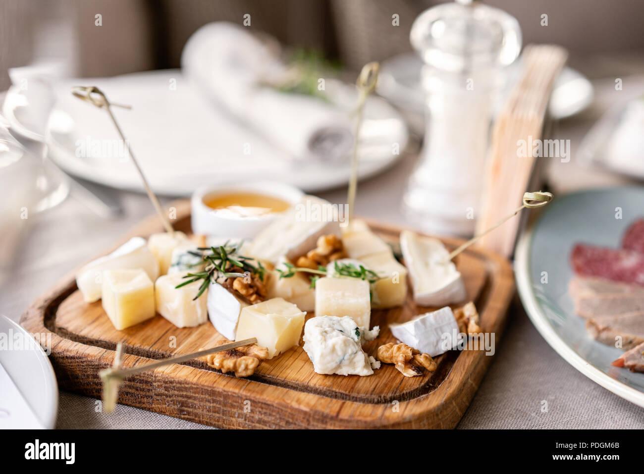 Plato de queso. Una deliciosa mezcla de queso con nueces, miel sobre la mesa de madera. Plato de degustación en una placa de madera. Alimentos para el vino. Imagen De Stock