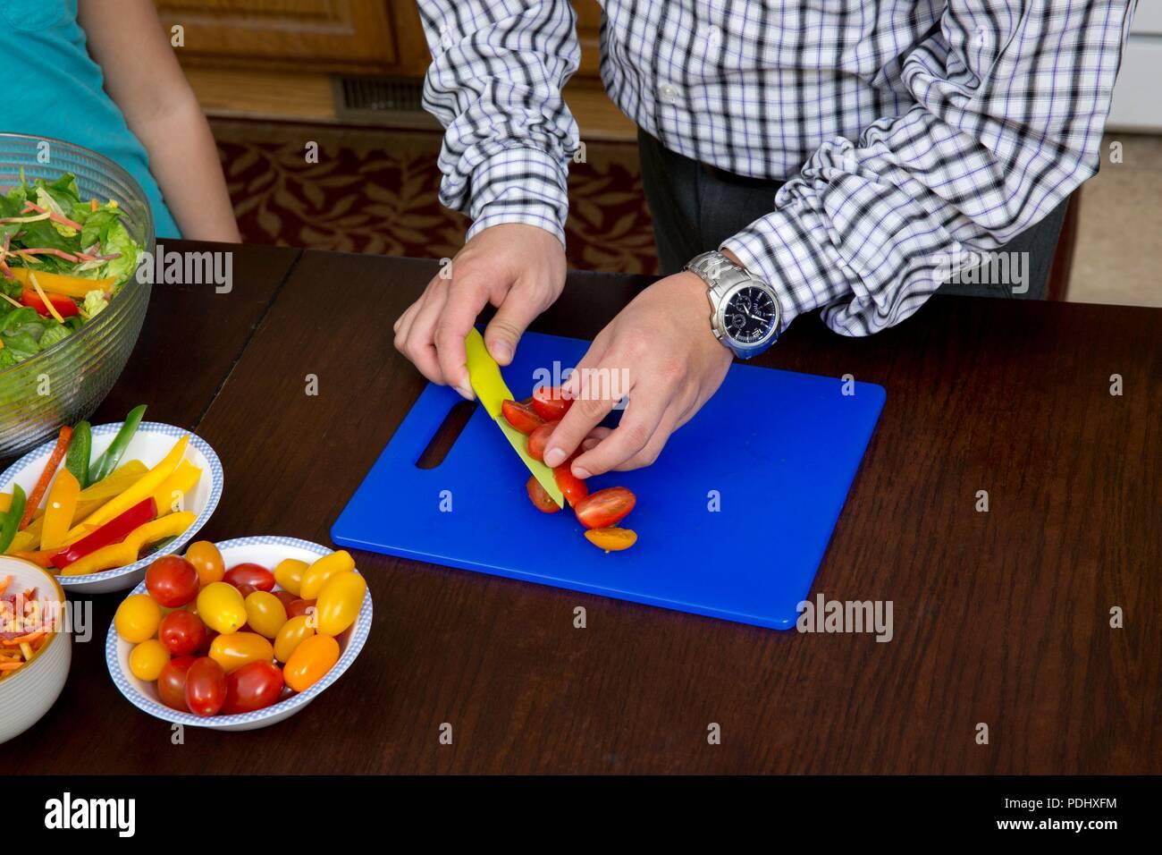 Hombre rebanar tomates con un bonito sobre una placa de corte azul en una cocina de hogar Imagen De Stock
