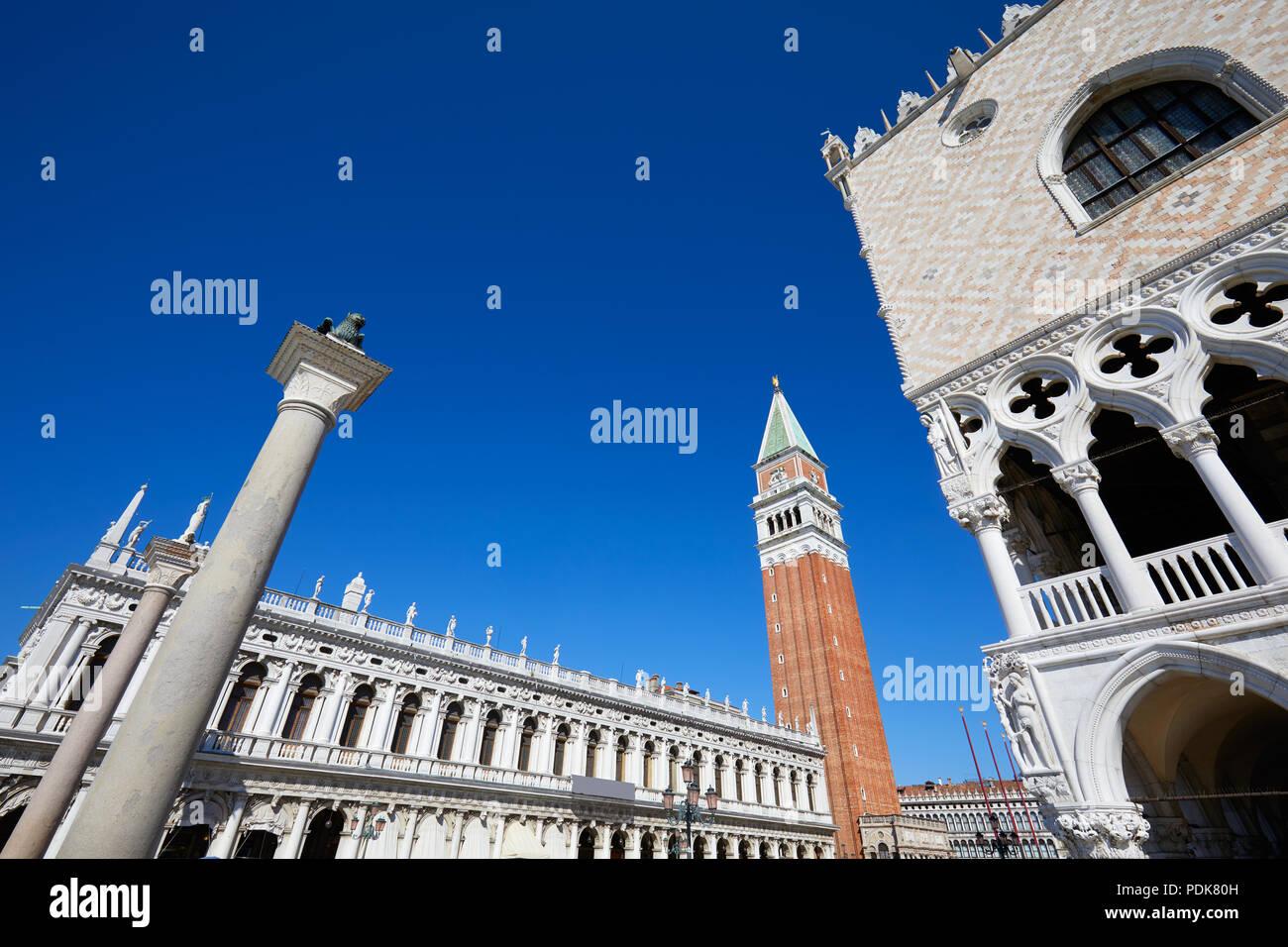El campanario de San Marcos, la biblioteca Marciana Nacional y el palacio Doge bajo ángulo de visión, el azul claro del cielo en Venecia, Italia Imagen De Stock