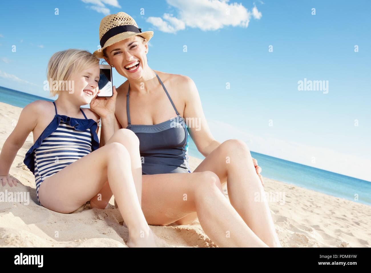 0e2f07a91654 Feliz joven madre e hija en traje de baño en la playa, hablando por ...